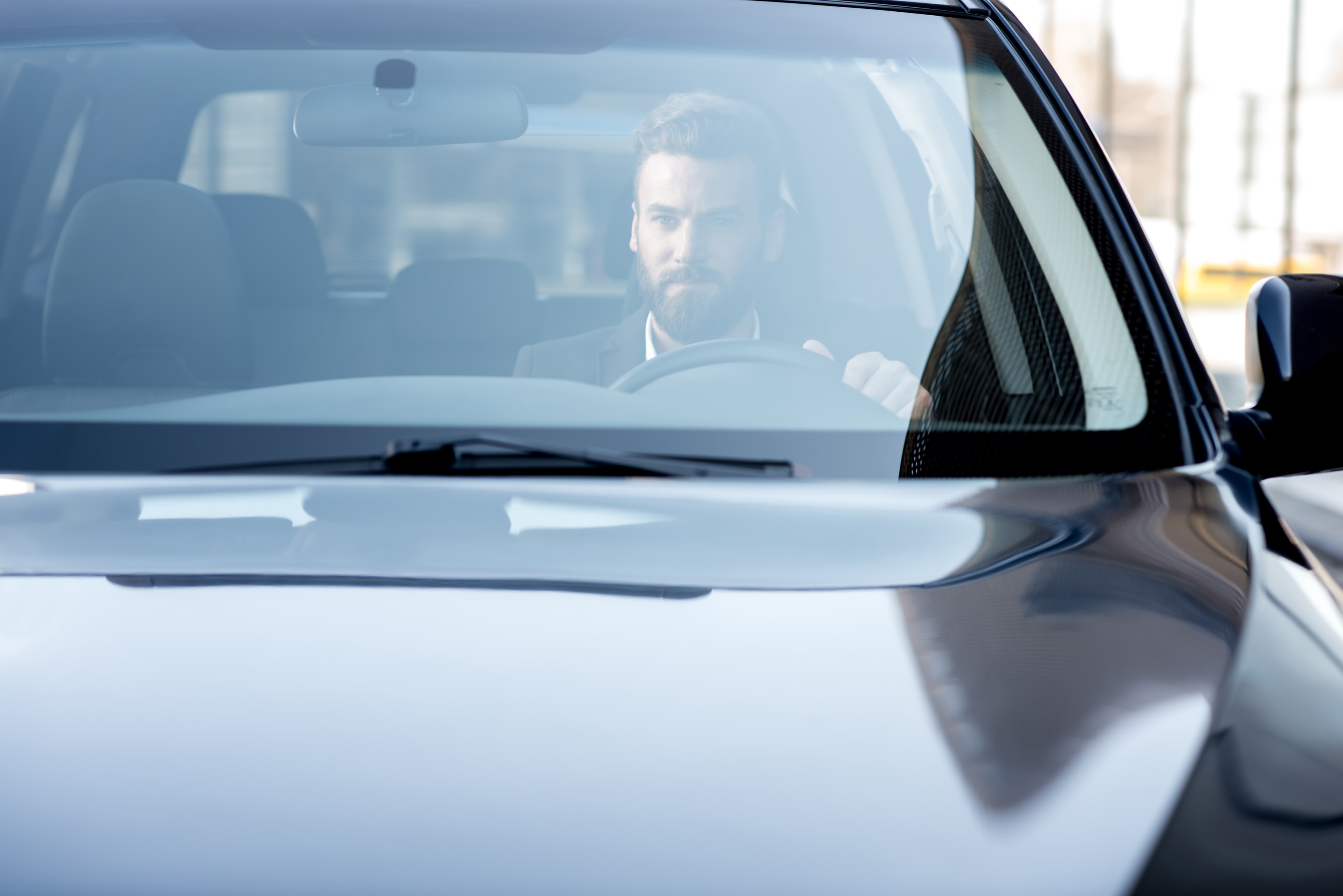 handsome-businessman-driving-car-city-view